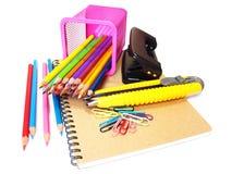 cuaderno y efectos de escritorio de los lápices del color aislados en blanco Foto de archivo libre de regalías