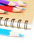 cuaderno y efectos de escritorio de los lápices del color aislados en blanco Imágenes de archivo libres de regalías
