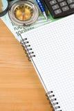 Cuaderno y euro con el compás Foto de archivo
