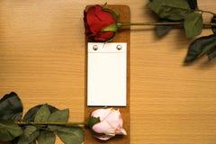 Cuaderno y flores color de rosa en la tabla de madera Foto de archivo libre de regalías