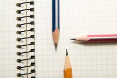 Cuaderno y lápices abiertos encendido sobre blanco Fotos de archivo libres de regalías