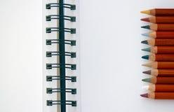 Cuaderno y lápices en blanco fotografía de archivo