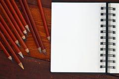 Cuaderno y lápices en blanco fotos de archivo