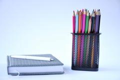 Cuaderno y lápices en la tabla fotos de archivo libres de regalías