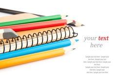 Cuaderno y lápices y texto Foto de archivo libre de regalías