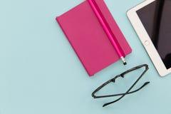 Cuaderno y lápiz de la tableta en fondo azul Fotografía de archivo libre de regalías
