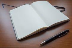 Cuaderno y lápiz del papel en blanco en fondo de madera marrón de la tabla Imagenes de archivo