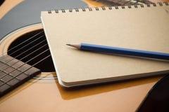Cuaderno y lápiz del primer en la guitarra imagen de archivo