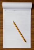 Cuaderno y lápiz en el fondo de madera imagenes de archivo