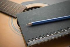 Cuaderno y lápiz en la guitarra fotografía de archivo libre de regalías