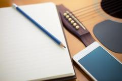 Cuaderno y lápiz en la guitarra fotos de archivo