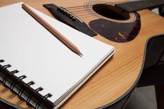 Cuaderno y lápiz en la guitarra Fotos de archivo libres de regalías