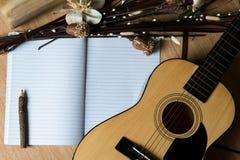 Cuaderno y lápiz en la guitarra, escribiendo música Fotografía de archivo libre de regalías