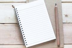 Cuaderno y lápiz en la tabla de madera Imagenes de archivo