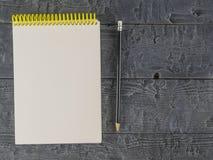 Cuaderno y lápiz negro en una tabla de madera oscura La visión desde la tapa imagen de archivo