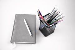 Cuaderno y l?pices en la tabla imágenes de archivo libres de regalías