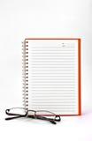 Cuaderno y lentes anaranjados Imagen de archivo