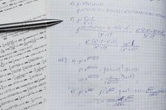 Cuaderno y libro con ecuaciones y funciones de las matemáticas Fotos de archivo