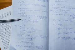 Cuaderno y libro con ecuaciones y funciones matemáticas Fotos de archivo