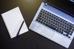 Cuaderno y ordenador en el fondo de madera Foto de archivo