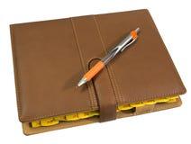cuaderno y pluma aislados en el fondo blanco Foto de archivo
