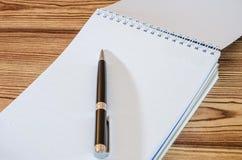 Cuaderno y pluma blancos en un fondo de madera, primer foto de archivo