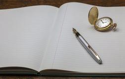 Cuaderno y pluma con el reloj de oro imagen de archivo libre de regalías