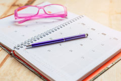 Cuaderno y pluma con formato del calendario de los vidrios Imágenes de archivo libres de regalías