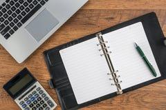 Cuaderno y pluma con la calculadora en el escritorio fotografía de archivo