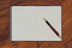 Cuaderno y pluma de la tapicería imagen de archivo