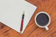 Cuaderno y pluma de la tapicería con café foto de archivo libre de regalías