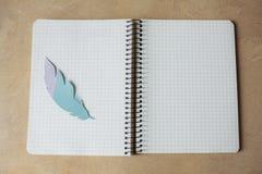 Cuaderno y pluma en la tabla Foto de archivo libre de regalías
