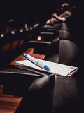Cuaderno y pluma en los apoyabrazos durante una conferencia Fotos de archivo libres de regalías