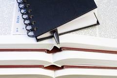 Cuaderno y pluma en los libros foto de archivo