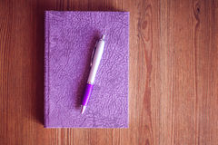 Cuaderno y pluma púrpuras en la tabla de madera Imágenes de archivo libres de regalías