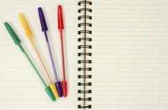 Cuaderno y plumas coloridas Foto de archivo libre de regalías