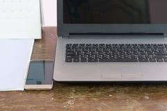 Cuaderno y smartphone con los accesorios imagen de archivo