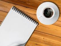 Cuaderno y taza blanca de café caliente Fotos de archivo libres de regalías