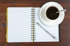 Cuaderno y taza de café Foto de archivo libre de regalías