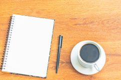 Cuaderno y taza negra del café con leche de la pluma en el fondo de madera de la tabla Foto de archivo libre de regalías