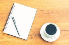 Cuaderno y taza negra del café con leche de la pluma en el fondo de madera de la tabla Fotografía de archivo