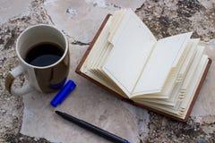 cuaderno y taza y pluma vacíos de café con el espacio de la copia Foto de archivo