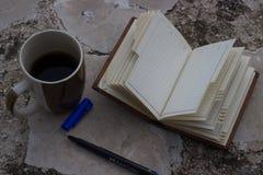 cuaderno y taza y pluma vacíos de café con el espacio de la copia foto de archivo libre de regalías