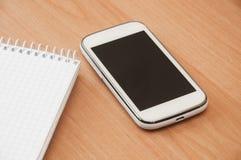 Cuaderno y teléfono móvil en la tabla Imágenes de archivo libres de regalías
