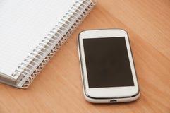 Cuaderno y teléfono móvil en la tabla Imagenes de archivo