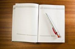 Cuaderno y una pluma Fotografía de archivo libre de regalías