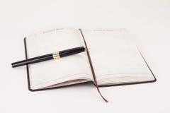 Cuaderno y una pluma Imagen de archivo