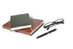 Cuaderno y vidrios de la pluma en un fondo blanco Fotografía de archivo libre de regalías