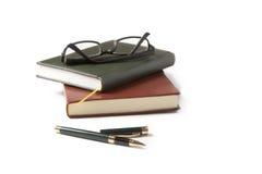 Cuaderno y vidrios de la pluma en un fondo blanco Fotos de archivo