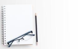 Cuaderno y vidrios del papel en blanco en el fondo blanco de la tabla Imagen de archivo libre de regalías